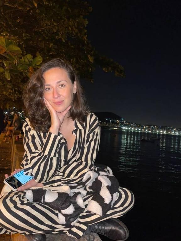 Jovem vestida de roupa listrada de preto e branco posa com mar ao fundo à noite