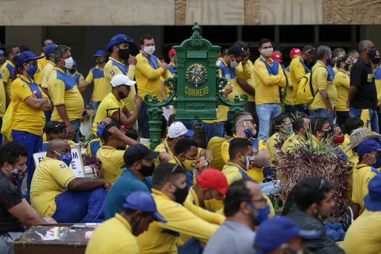 Funcionários dos Correios, uniformizados, reunidos frente à sede do órgão; ao centro, vê-se uma caixa de correio