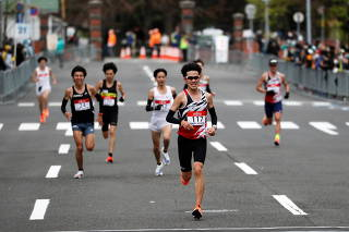 Runners cross the finish line while small groups of spectators are seen during the half-marathon of the Hokkaido-Sapporo Marathon Festival 2021