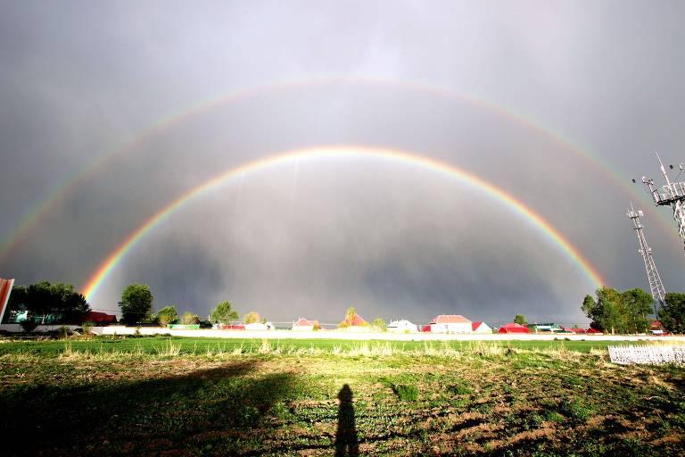Um arco-íris bem definido emparelhado a uma versão maior, um pouco mais apagada, que se curva logo acima