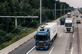 A truck draws electric power from overhead wires as it is driven along a highway near Erzhausen, Germany, on July 9, 2021. (Felix Schmitt/The New York Times)