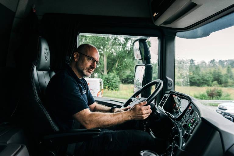Homem de camiseta sentado em cabine de caminhão