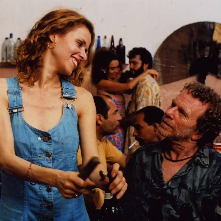 Mulher abre lata de cerveja enquanto homem a observa