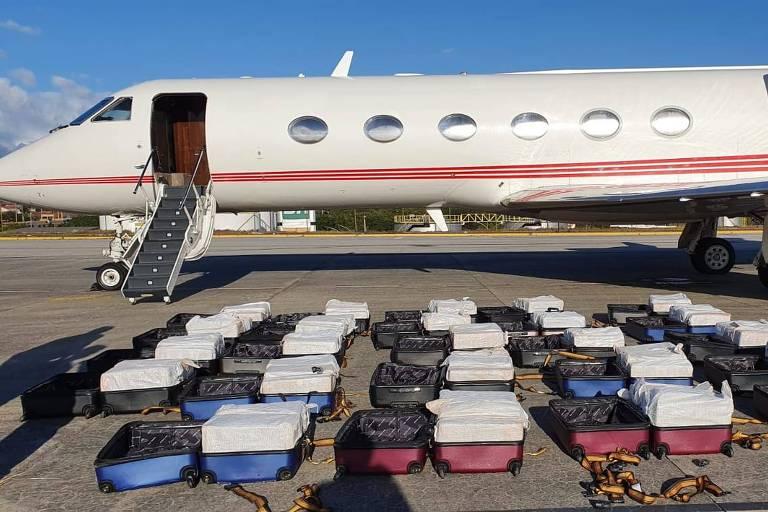 Imagem mostra dezenas de malas com cocaína dentro, espalhadas no chão do aeroporto, e um avião ao fundo