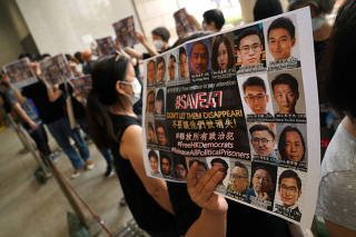People hold signs to support pro-democracy activists charged with violating the national security law at West Kowloon Magistrates? Courts, in Hong Kong