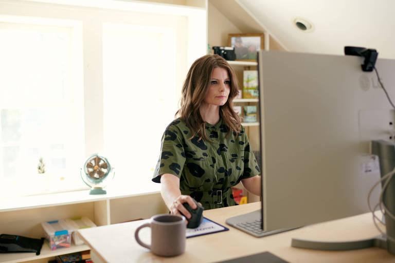 Mulher sentada em mesa, com computador