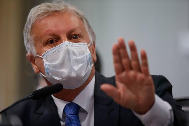 Um homem de cabelos brancos e máscara, com uma das mãos levantada enquanto fala ao microfone de mesa