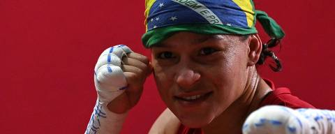 Brazil's Beatriz Ferreira (red) celebrates after winning against Finland's Mira Marjut Johanna Potkonen after their women's light (57-60kg) semi-final boxing match during the Tokyo 2020 Olympic Games at the Kokugikan Arena in Tokyo on August 5, 2021. (Photo by Luis ROBAYO / AFP)