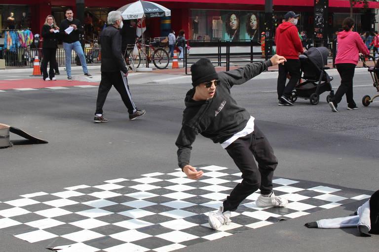 B-boys se apresentam dançando break ao som de batidas do funk americano de James Brown, remixado com uma música do rapper Sabotage.