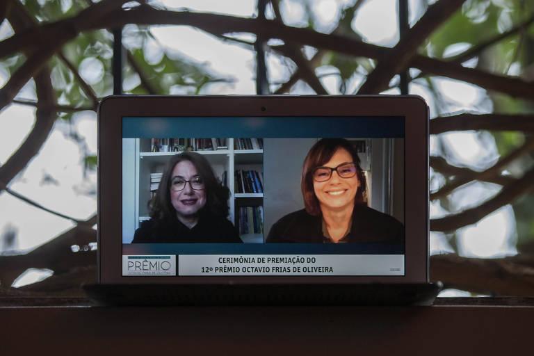Computador sobre uma mesa; na tela do notebook, duas mulheres, em ambientes separados, em teleconferência; atrás do computador, é possível ver árvores