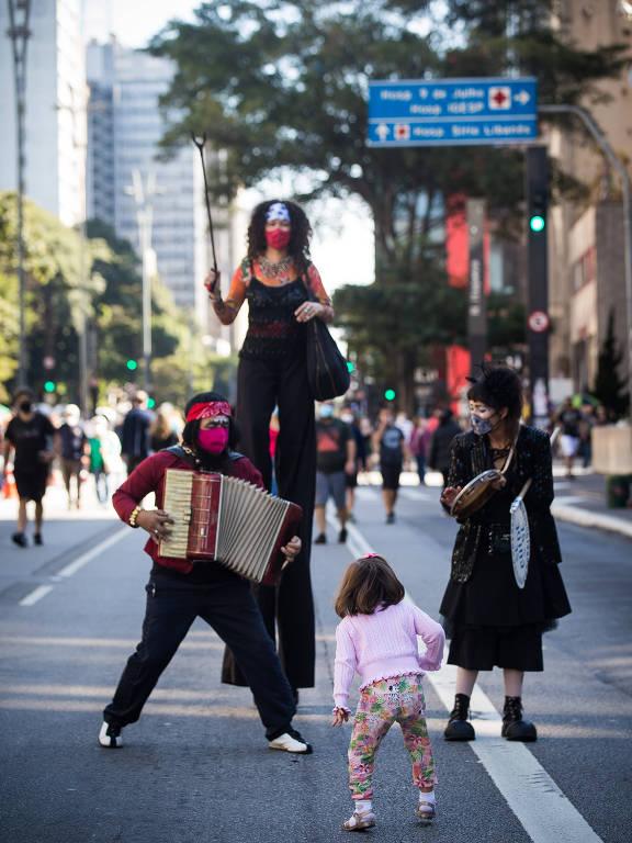 Criança se diverte com artistas circenses na Paulista fechada para carros