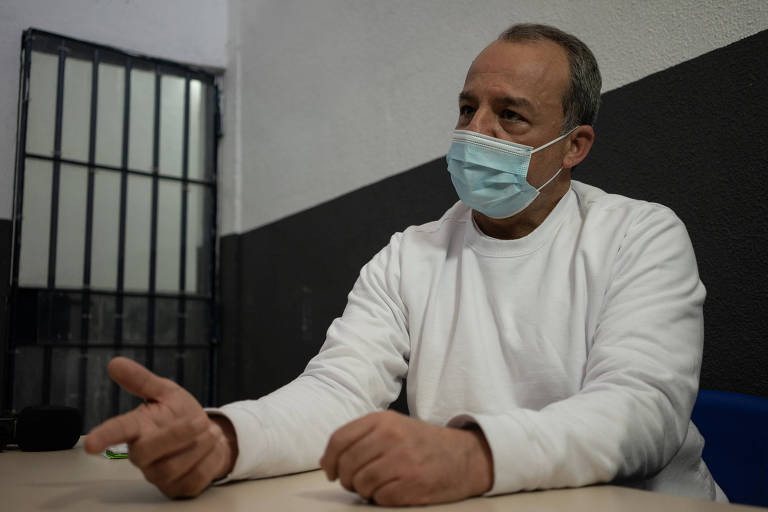 Sérgio Cabral, de blusa branca e máscara, está sentado em uma mesa