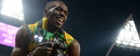 ORG XMIT: 2761 Jamaica's Usain Bolt takes pictures with a camera of a photographer after winning gold in the men's 200m final at the athletics event during the London 2012 Olympic Games on August 9, 2012 in London. Usain Bolt retained his 200m title on Thursday to become the first man to achieve the sprint double at consecutive Olympics.  AFP PHOTO / FRANCISCO LEONG