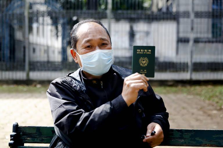 Um homem de máscara está sentado em um banco. Ele segura e mostra com uma mão um passaporte.