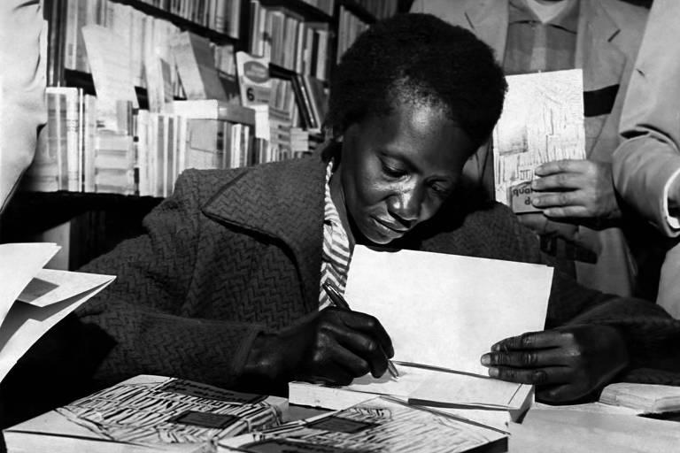 Mulher negra de cabelos curtos vestida com casaco elegante, escrevendo com caneta numa das primeiras folhas de um livro. Há outros livros sobre a mesa e uma estante ao fundo, e dois homens ao fundo com o livro, à espera da escritora.