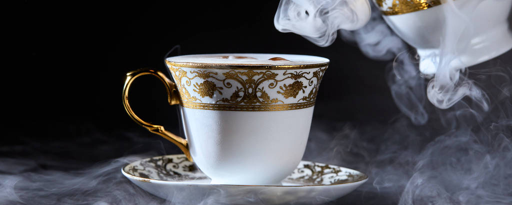Na imagem há uma xícara branca com detalhes dourados