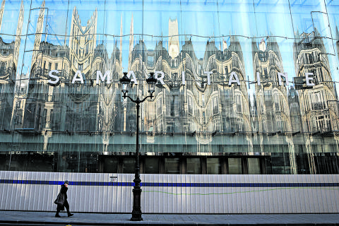A man walks along the new facade of the former department store La  Samaritaine after being renovated, on April 8, 2021 in Paris. (Photo by Ludovic MARIN / AFP)