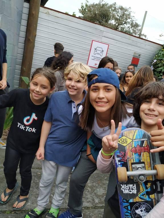 Três crianças abraçam adolescente de boné azul