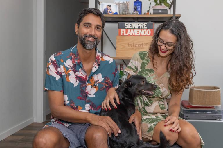 Homem de camiseta florida à esquerda senta ao lado de mulher, com cachorro no colo