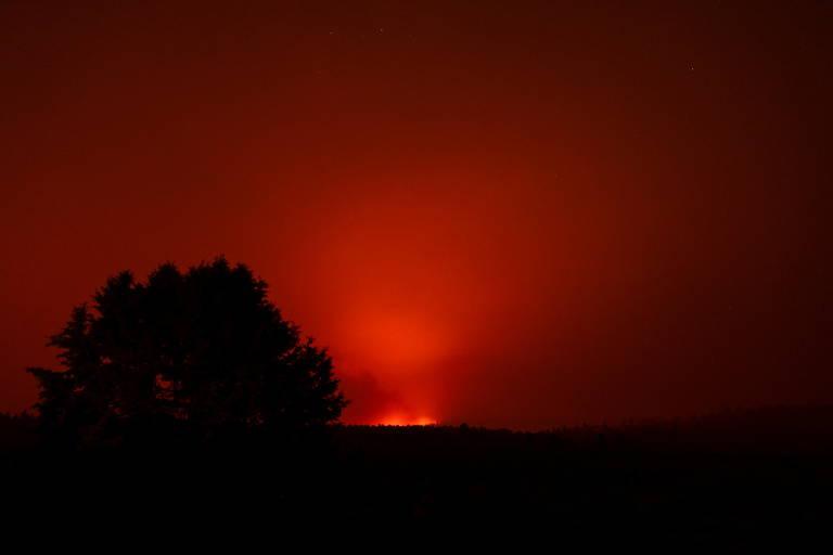 Céu avermelhado sobre colina e árvores