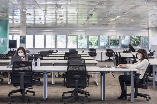 Empresas voltam a ocupar os escritorios, agora no modelo hibrido: Funcionarias Michelle Pacoal,28 e Adriana Lima,42, gerentes de Planejamento, trabalham em um dos almplos  escritorios da C & A em Alphaville. moda C&A, que reformulou sua sede. Escritorios estao porontos para receber 700 dos 1,5 mil funcionarios, mas por enquanto apenas 350 posicoes de trabalho estoo liberadas. Mesas sao agendadas por QR Code