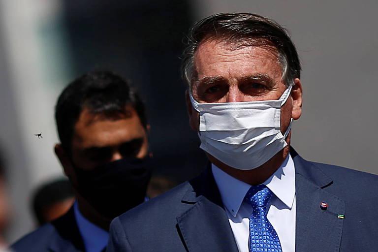 Bolsonaro de máscara branca. Atrás dele, outro homem de máscara preta