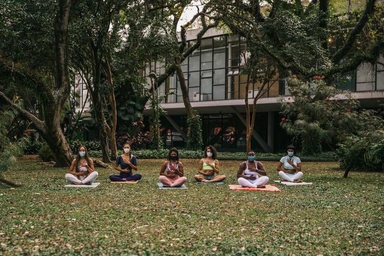 Seis mulheres negras estão sentadas em um tapete de ioga em um gramada. Ao redor, há vegetação.