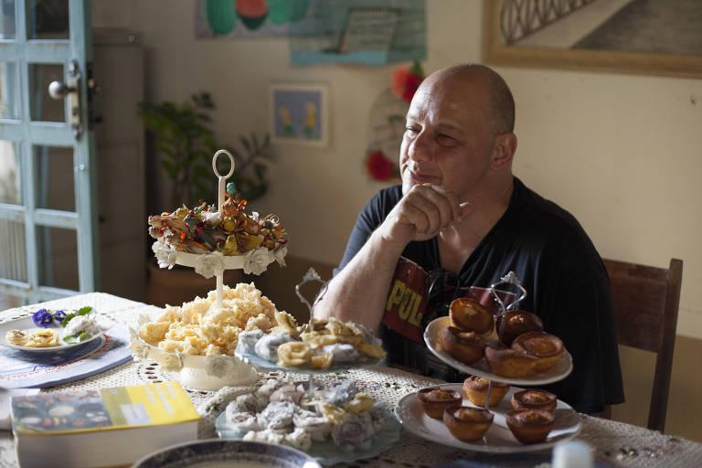 Homem branco senta em frente à mesa rodeado de doces