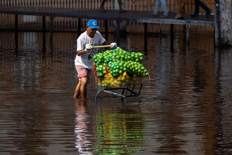 Homem empurra carrinho com frutas em rua inundada em Manaus, que enfrentou, nos últimos meses, a maior cheia já registrada do rio Negro