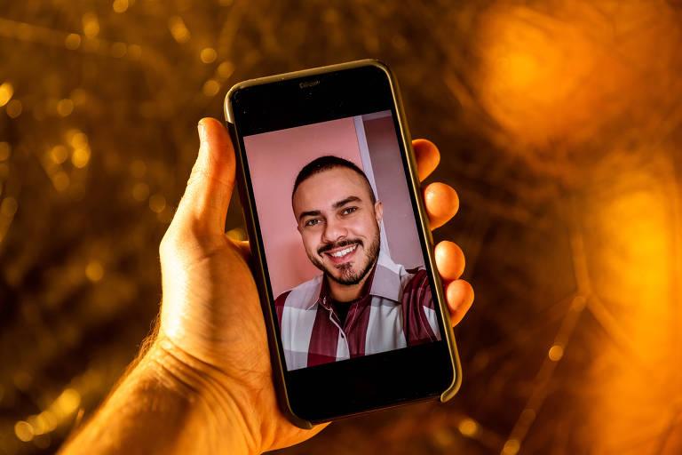 Uma mão segura um celular com a imagem de André