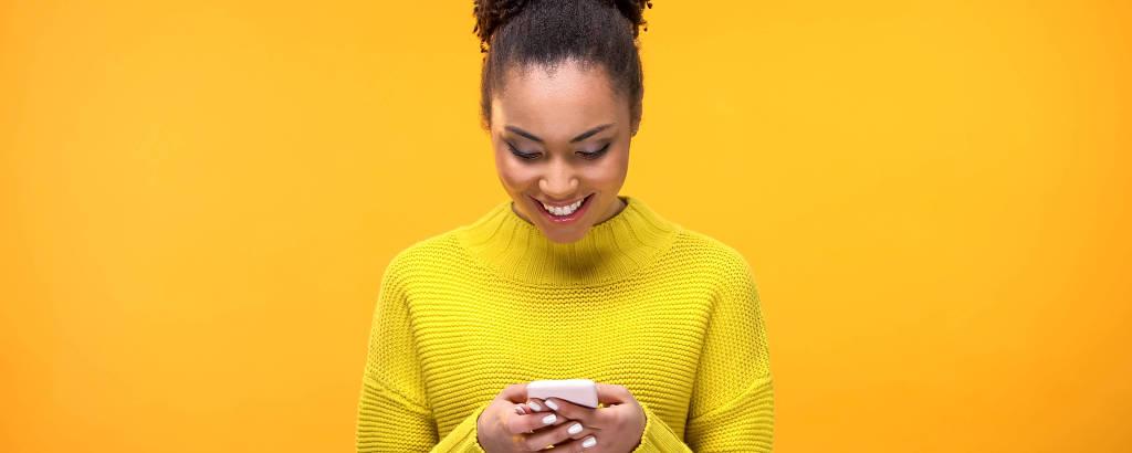 Mulher negra com roupa amarela segura aparelho de celular em mãos