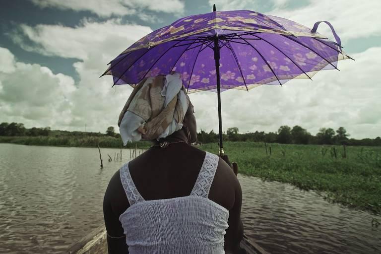 Uma mulher negra em uma jangada segura um guarda-chuva