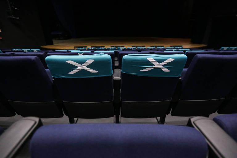 Na imagem duas poltronas de teatro estão com uma capa azul clara com um X branco que indica a proibição de sentar no local