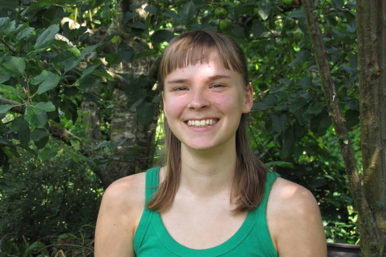 menina loira de camiseta verde sorri em frente a árvores