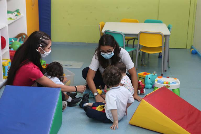 Professoras e crianças, de máscara, brincam durante aula em escola particular de São Paulo