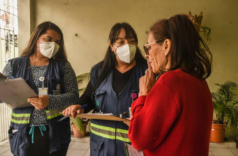 Catarina Ferreira dos Santos, 62, explica às agentes comunitárias de saúde Karla Farias Atílio (blusa preta)  e Letícia Aparecida Nunes da Silva que não retornou para a segunda dose da AstraZeneca, marcada para 29 de julho, porque apresentou sintomas gripais