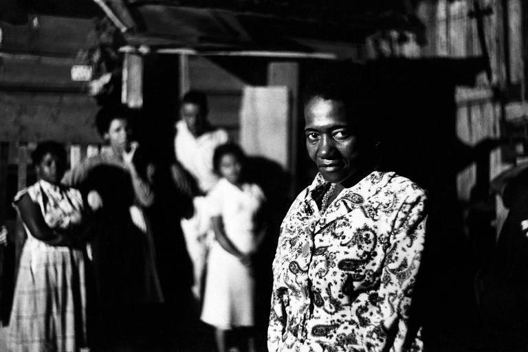 Mulher negra, vestida com camisa florida, em primeiro plano olhando a câmera com firmeza. Há outras quatro pessoas ao fundo, uma mulher, um adolescente e duas meninas, todos negros, mas pouco nítidos.