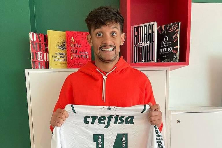 O jogador Gustavo Scapa sorrindo, segurando sua camisa do Palmeiras e na frente de uma estante com livros