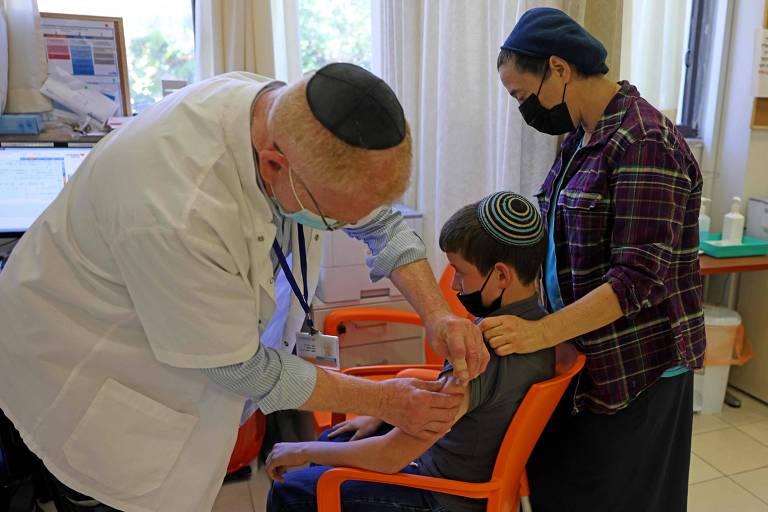 Homem de cabelo claro, avental branco e quipá aplica injeção em garoto de camiseta, cabelo e quipá pretos; ao lado dele, em pé, uma mulher