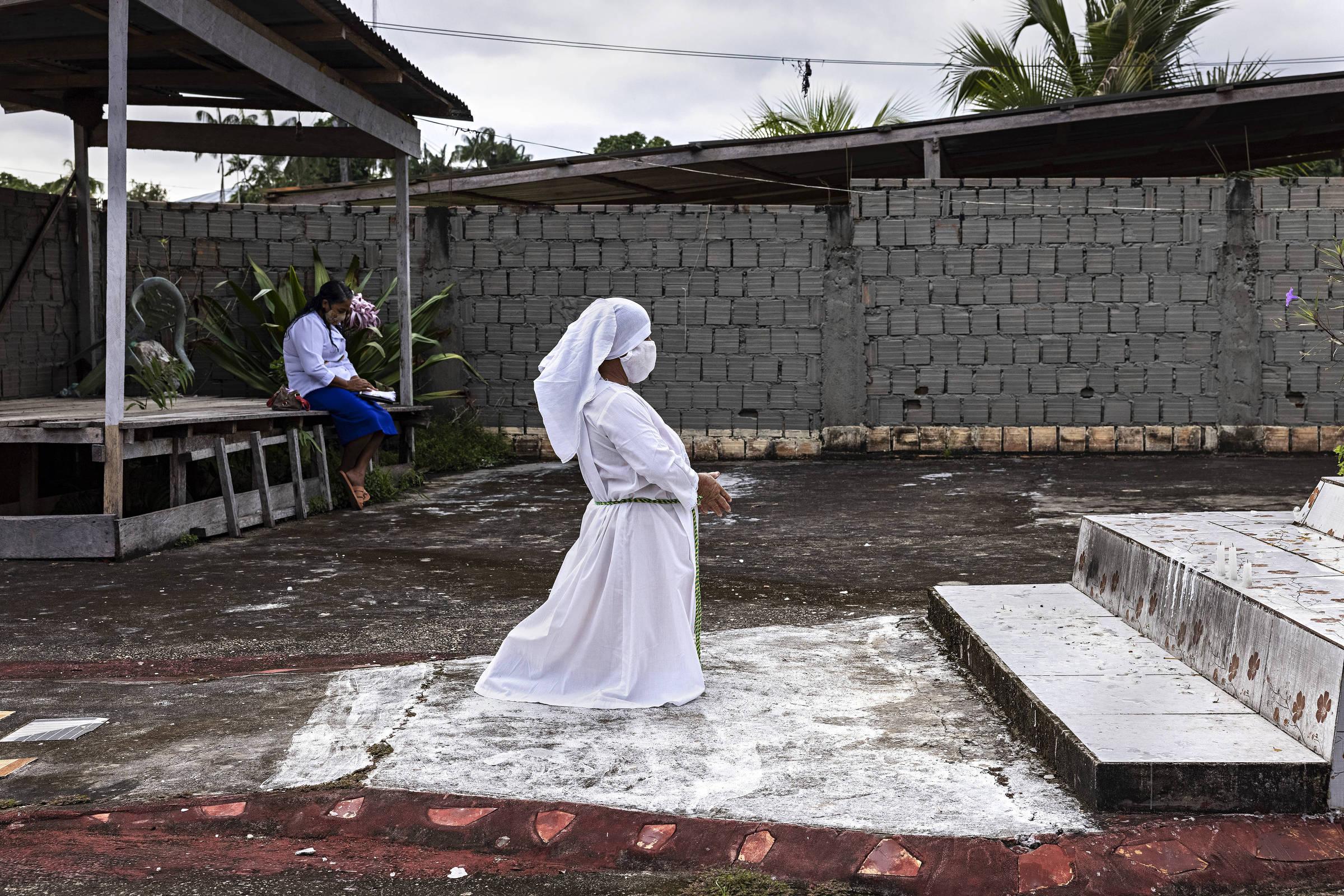 Fiel da Irmandade da Cruz ora em frente à igreja