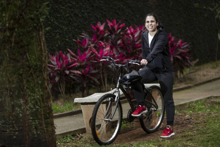 mulher de agasalho segura uma bicicleta e sorri