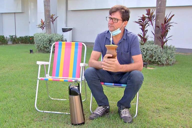 homem sentado em gramado com chimarrão