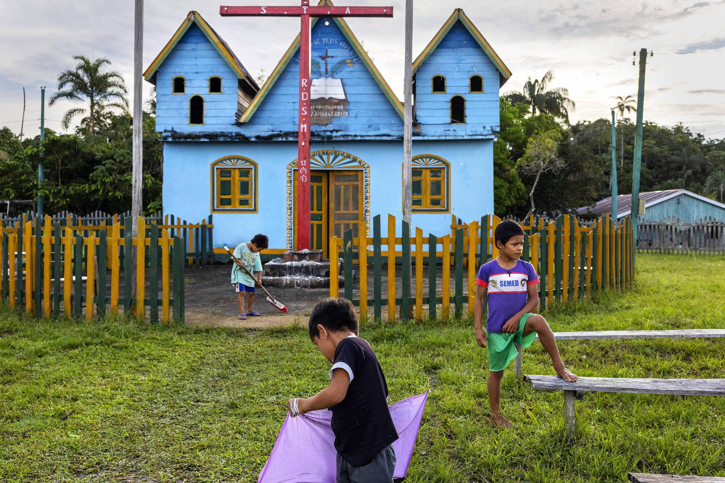 Crianças brincam em frente à igreja da Irmandade da Cruz na aldeia São Pedro do Norte, às margens do rio Javari, na fronteira com o Peru