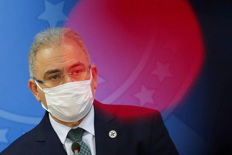 De máscara branca e terno escuro, Marcelo Queiroga, branco e de cabelos grisalhos curtos, em frente a painel com bandeira do Brasil