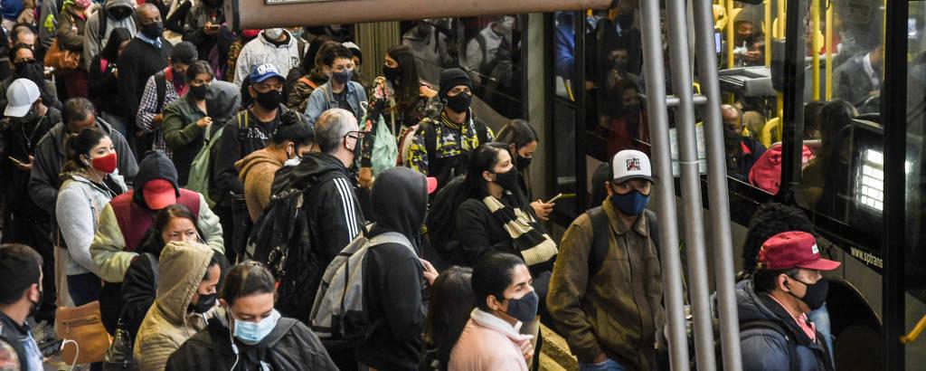 Pessoas de máscara aglomeradas em frente a ônibus