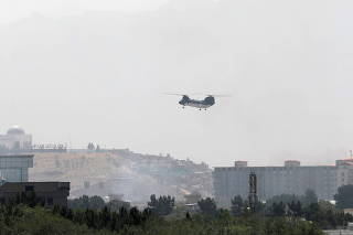 Military transport helicopter flies over Kabul