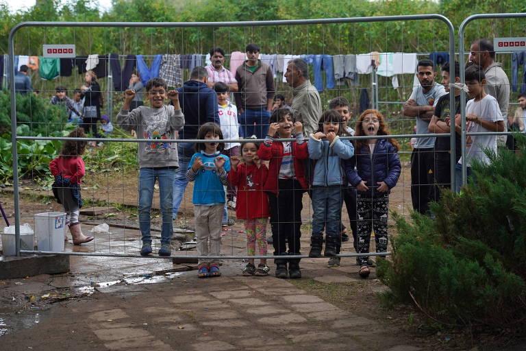 Oito crianças de diferentes tamanhos, meninos e meninas, olham através de grade