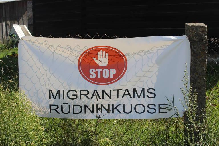 Cartaz em lituano, com símbolo de pare vermelho, pede o fim da chegada de imigrantes