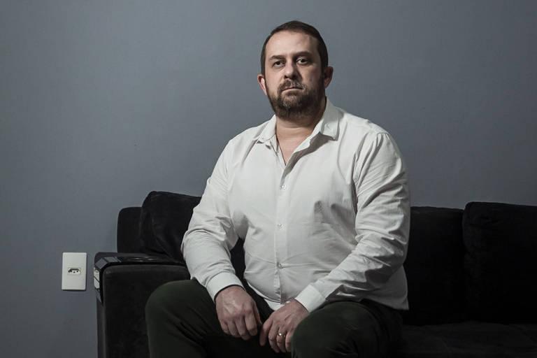 O engenheiro Cleber, que busca emprego há quase um ano e meio, sentado no sofá de sua casa