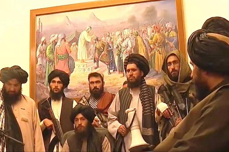 Homens armados com quadro ao fundo